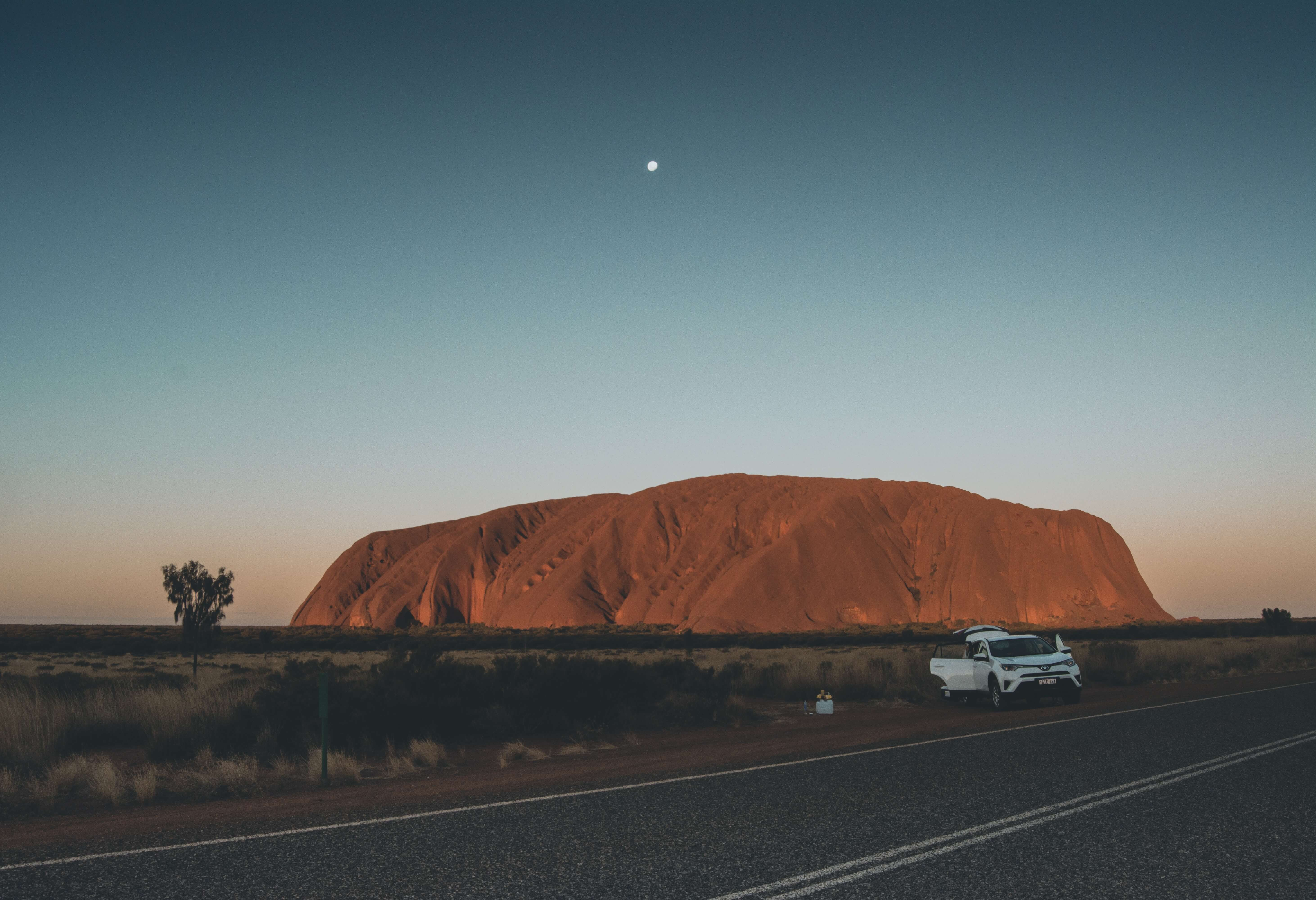 Watch the sunset at Uluru on a working holiday in Australia